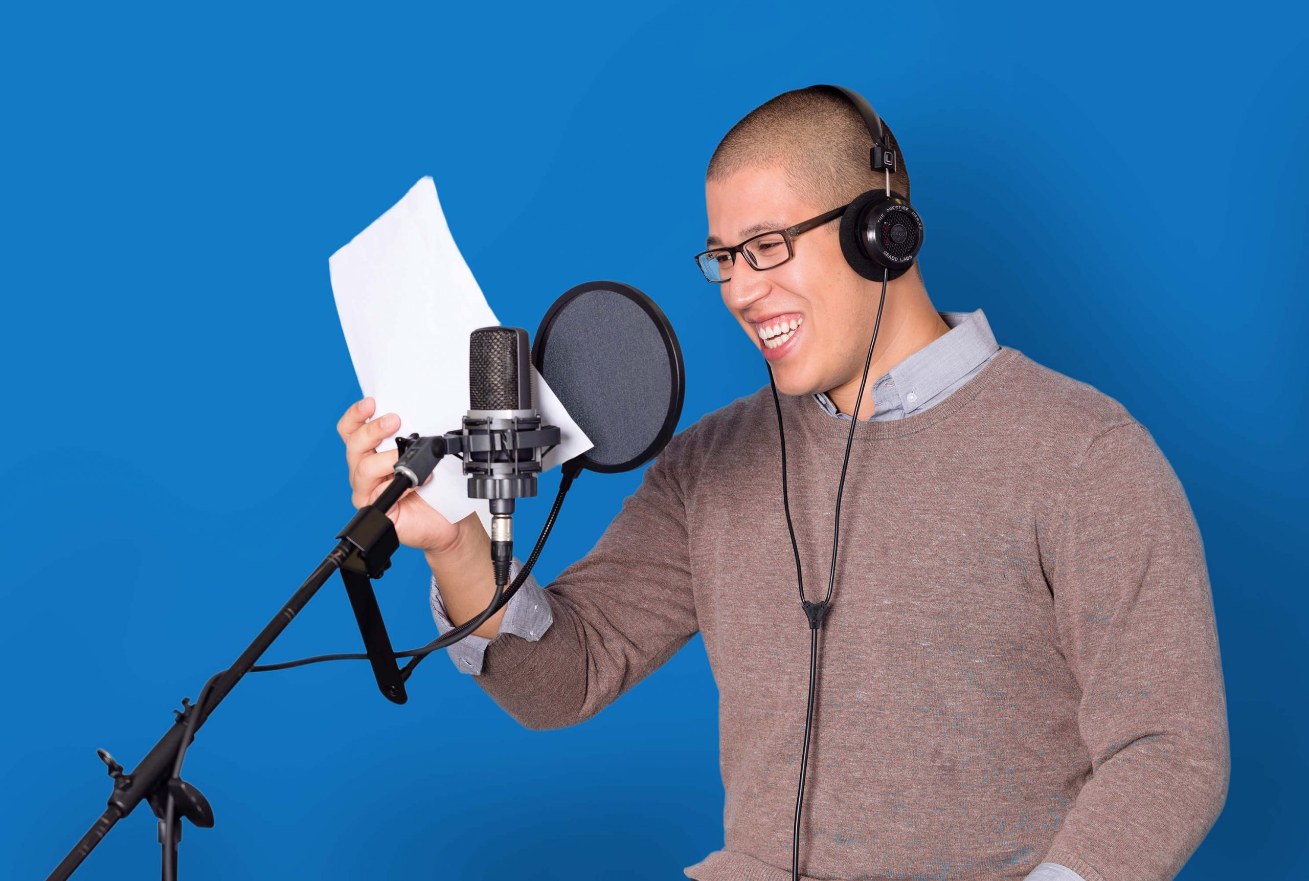 A voice actor sitting in front of a microphone and reading from a script against a blue background.