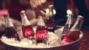 Client: David Studio alt text: A man grabs a Coca-Cola bottle from a bucket full of ice.
