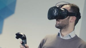 A man with a VR headset, holding up a controller.
