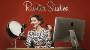 A woman sitting at a desk with a computer and a studio light, and she is speaking into a vintage candlestick phone.