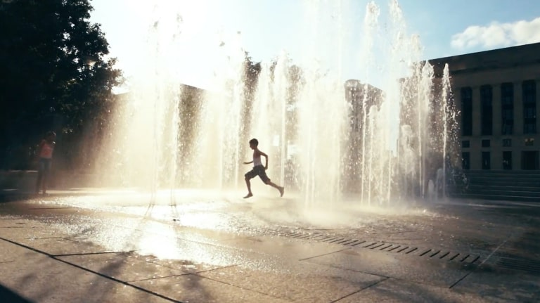 A little boy running through a splash pad with water spraying up from the ground. The sunlight behind the splash pad gives the water a warm glow