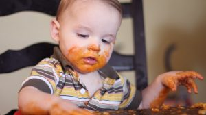 A baby sitting in a high chair and playing with his food.The baby food is smeared across his face and hands.