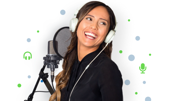 A smiling voice actress wearing headphones and standing beside a microphone.