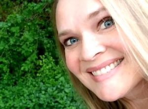 Emily Flegal, a woman with blond hair and blue eyes, taking a selfie in a forest.